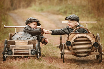 Portrait of two boys on improvised racers cars