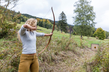 Woman with bow aiming on target in field