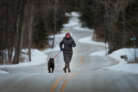 Woman walking with dog in winter