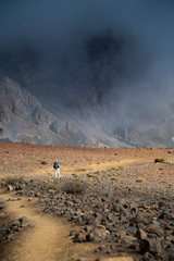 A woman in her thirties carrying an infant hikes in the high-elevation volcanic Haleakala crater.