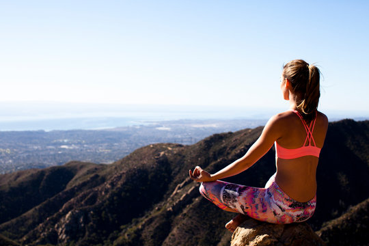A woman in multicolored pants sits with her legs crossed while on Lower Gibraltar Rock in Santa Barbara, California.  Lower Gibraltar Rock provides great vistas of Santa Barbara and the Pacific Ocean.