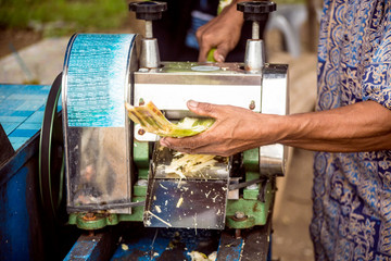 A Man Uses A Machine To Squeeze Sugar Cane Juice Out In Java, Indonesia