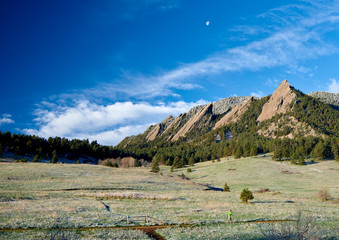Person trail running beneath the Flatirons in Boulder and a moon above.