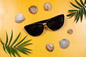 Fototapeta Flat lay na żółtym tle, okulary przeciwsłoneczne i muszelki. Inspiracja na wakacje, lato, czas wolny obraz