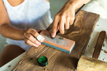 Young woman carves picture on wood