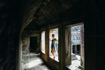 Girl is exploring ancient ruins in Cambodia