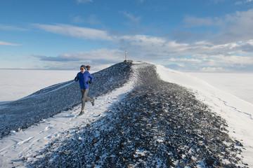 Woman trail running on Hut Point Peninsula on Ross Island, Antarctica.