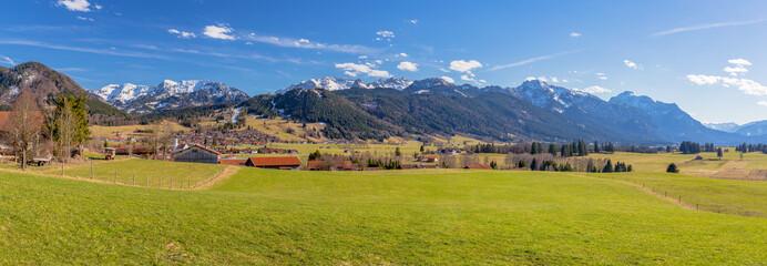 Blick über Bayerniederhofen und Buching auf die Allgäuer Alpen