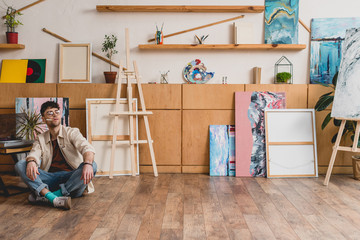 artist in pink shirt and blue jeans sitting on floor in spacious painting studio and smoking cigarette
