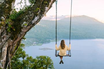 Woman sitting on swing against Lake Buyan, Bedugul, Bali, Indonesia