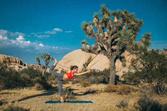 A young woman  in yoga dancer pose, Joshua Tree