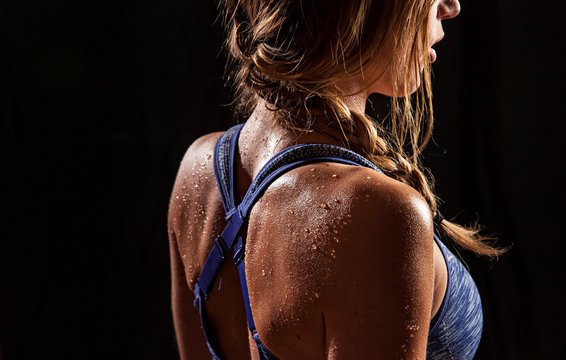 Fit woman's shoulders and back beaded with sweat.