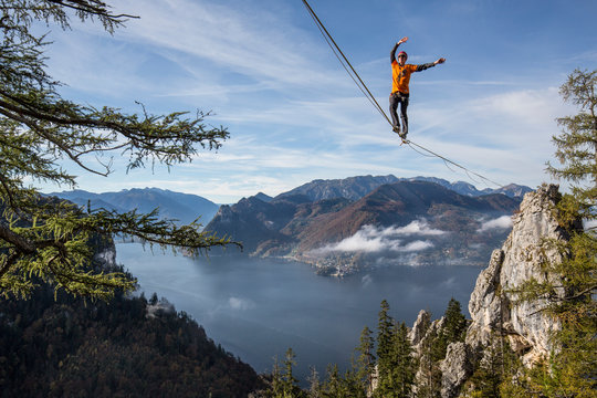 Person walking on line above Traunsee lake in Upper Austria, Austria