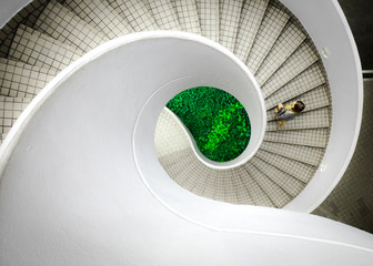 Woman walking up spiral staircase decorated with checked pattern