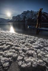 Woman paddleboarding in Lake Minnewanka, Banff National Park, Alberta, Canada