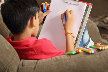 Portrait of Indian boy drawing with colorful sketch pen