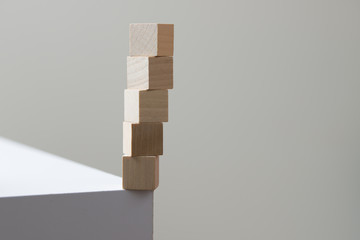 Wooden cubes in balance at the edge of the table for risk of falling concept