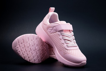 Pair of unbranded pink color sport or running shoes on a black background