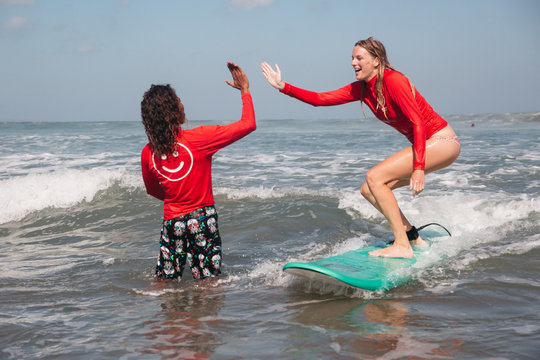 Surf instructor coach guide and student on surfboard giving high five at surf school lesson, learning surfing at Seminyak beach, Bali, Indonesia