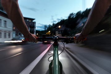 Cyclist rides on a bike lane at dusk - First-person view of cyclist