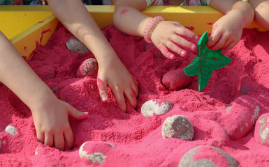 The child plays with his hands in the pink sand