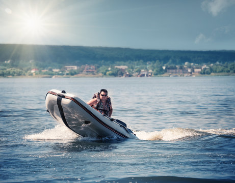Man in  life jacket driving rubber motor boat