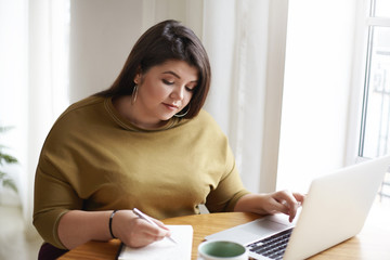 Picture of attractive young European female journalist wearng stylish earrings and knitted sweater making notes in diary while working on research for her new article, looking for information online