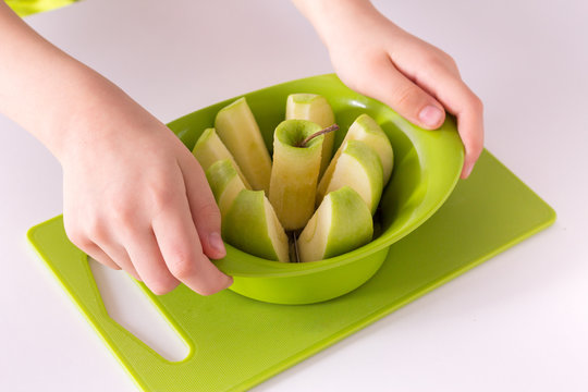 Children's hands holding an apple slicer and cutting green apple. Isolate on white background.