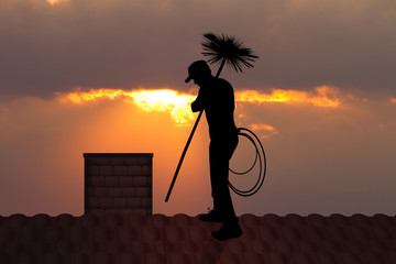 chimney sweep on roof at sunset