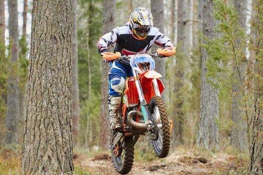 Motocross driver jumping with the bike at high speed on the race track.