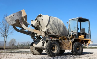 Self loading mini concrete mixer truck half covered with cement dust