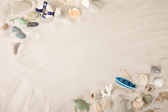 Beach summer theme. Summer background with sea shells and red star with sand on blue wooden planks. Copy space. Marine theme
