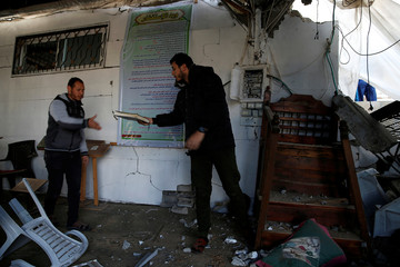 Palestinian hands a copy of the Koran from a mosque that was damaged in a nearby Israeli air strike in Gaza