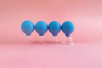 four blue cosmetic vacuum jars of different sizes made of glass and rubber on pink background