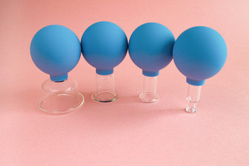 blue cosmetic vacuum jars of different sizes made of glass and rubber on pink background