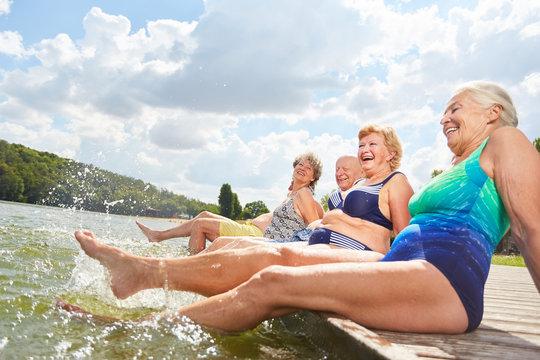 Aktive Senioren plantschen mit Füßen im Wasser