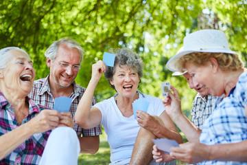 Senioren Freunde spielen Karten im Garten Wall mural
