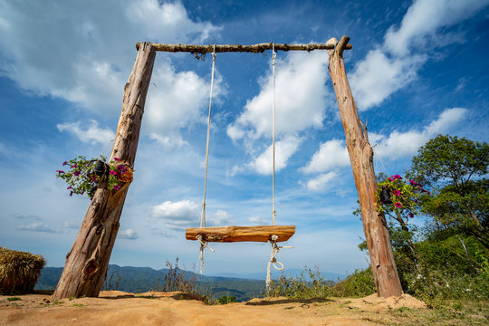 Wooden swing and blue sky on mountain background