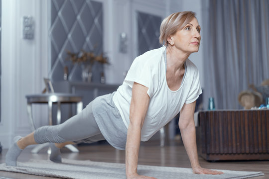 Middle -aged woman making yoga plank position on mat