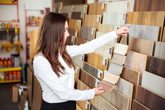 Beautiful young woman on position of manager or seller with dark hair looks at different types and colors of floor coloring in a small store