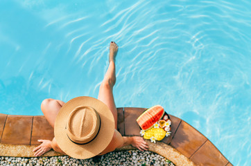Woman in straw hat sitting on swimming pool side  with plate of tropical fruits. Top view shot