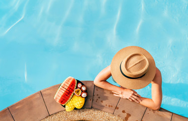 Woman in straw hat in pool with plate og tropical fruits