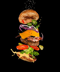 Tasty hamburger with flying ingredients on dark background. High resolution image.