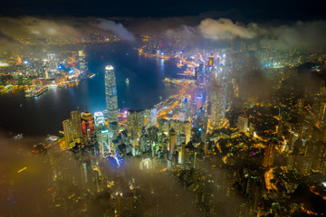 Wall Mural - Aerial view of Hong Kong City skyline at night over the clouds