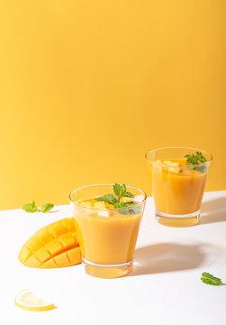 Fresh mango smoothie and ripe mango slice on yellow background. summer drink.