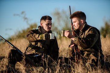 Rest for real men concept. Hunters with rifles relaxing in nature environment. Hunting with friends hobby leisure. Hunters friends enjoy leisure. Hunters satisfied with catch drink warming beverage Wall mural