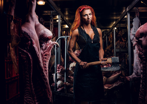 Strong female butcher in workwear posing with ax in a refrigerated warehouse in the midst of meat carcasses