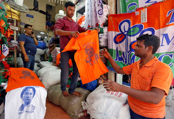 A customer buys a T-shirt with an image of Prime Minister Narendra Modi at a shop at a market ahead of India's general election, in Kolkata