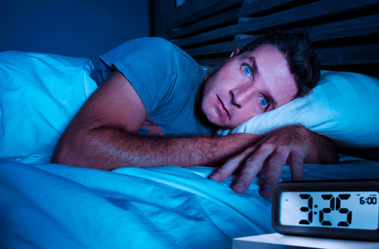 restless worried young attractive man awake at night lying on bed sleepless with eyes wide opened suffering insomnia sleeping disorder depressed