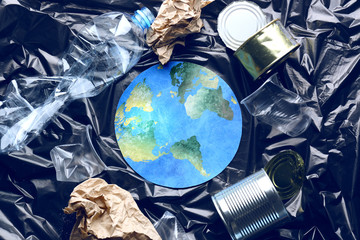Paper figure of earth and garbage on polyethylene film. Concept of environmental protection Wall mural